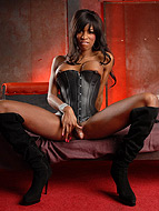 Red dungeon. Hot ebony ladyboy Natassia posing in lascivious black corset